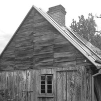 Image: A small, single-storey wooden dwelling with one visible window at a steep roof. The structure is surrounded by trees and vegetation