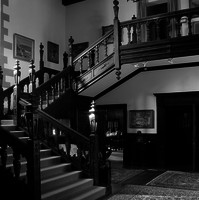 Image: An ornate wooden staircase in an historic house. Several ornate rugs and framed paintings are visible on the floors and walls surrounding the staircase