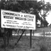 Image: sign amongst gum trees with buildings in background