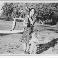 Image: Women holding fishing rod with fish next to small boy