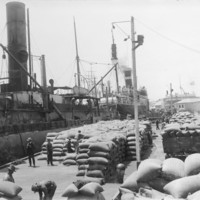 Image: large number of hessian bags being loaded or unloaded from steam ships