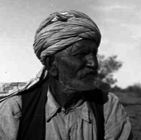 Image: An elderly man with a beard and turban stands in the central Australian desert