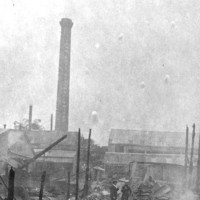 Image: A small group of people stand within the smouldering remains of a building. Charred wooden uprights and collapsed corrugated metal sheeting are all that remains of the structure