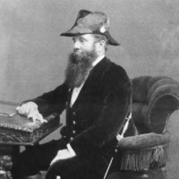 Image: a bearded man in three quarter profile and wearing a hat and sword sits at his writing desk.