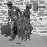Image: bronze sculpture of family group with suitcase