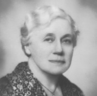 Image: Portrait photograph of a woman in her late fifties/early sixties with short light hair. She is wearing a cross necklace.