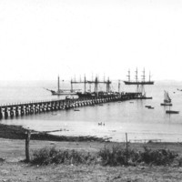Image: A jetty jutting out into the ocean surrounded by various size sailing ships.