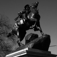 Image: The statue of a horse and rider mounting the crest of a hill