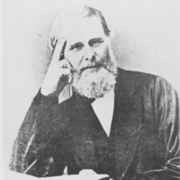 Image: bearded man seated with book