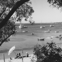 Image: Black and white photograph of people on a beach, with boats in the water in the distance.