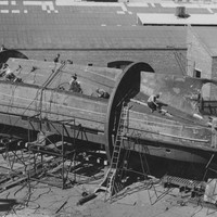 Image: The body of a tug boat upside down in the process of being constructed, numerous people, ropes and ladders surround the boat