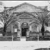 "Image: Black and white photograph of the front of a building. Palm trees stand on either side of the front of the building. The building reads ""ART GALLERY"""