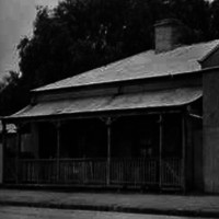 Image: a corrugated iron workshop with a gable roof and a central doorway flanked by a single window on either side. Next door is a small cottage with a verandah and central chimney.