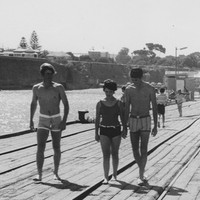 Image: People walking and others fishing with hand rods from a wooden jetty