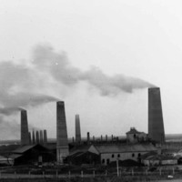Image: Several large brick chimneys are flanked by a number of buildings. A vague coastline is visible in the background
