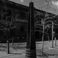 Image: metal post in front of large stone building